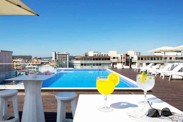 Take a swim at the rooftop pool with a view of Lisbon from Jupiter Lisboa Hotel
