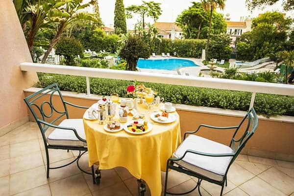 Have your breakfast at the balcony with a view of the pool and Lisbon at Olissippo Lapa Palace