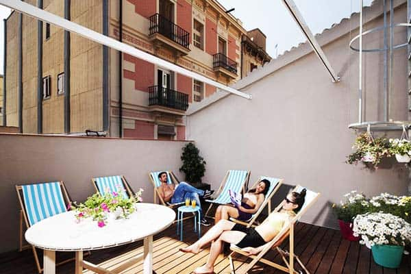 Do sunbathing at the rooftop terrace at Amistat Beach Hostel