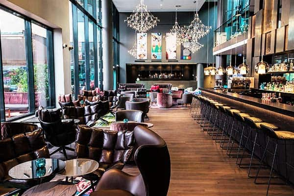 Motel One Wien-Hauptbahnhof features a bar decorated with Arne Jacobsen chairs and Swarovski chandeliers