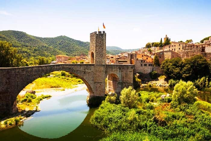 Walk on the fortified bridge and see the medieval town of Besalu, Spain
